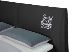 Tom Tailor felirat az ágy fejvégen